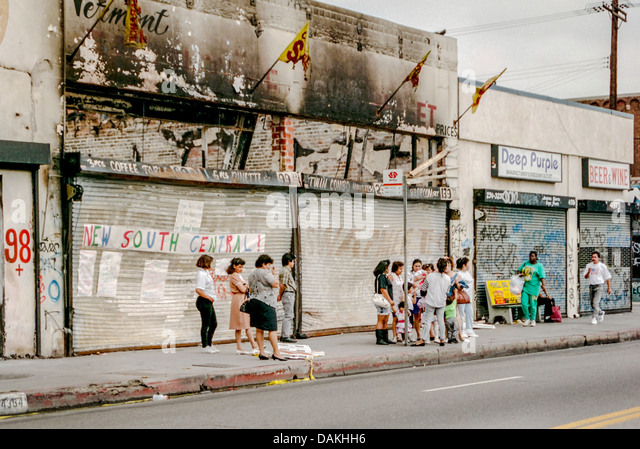 Multiethnic locals wait for a bus in front of fire damaged shops in South Central Los Angeles after the 1992 Rodney - Stock Image