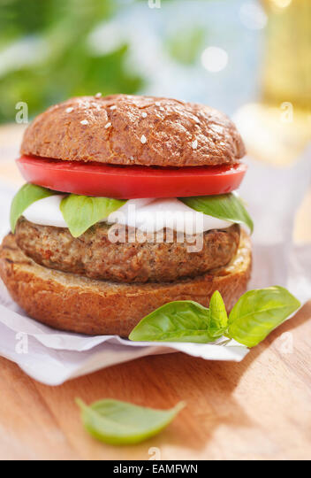 Italian style burger with mozzarella cheese, basil and tomatoes - Stock Image