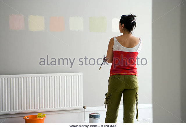 Woman looking at various paint colours on wall in undecorated room making decision rear view - Stock Image