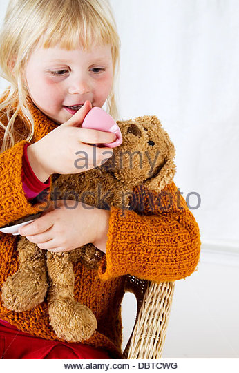 Portrait of girl (6-7) feeding teddy bear - Stock Image