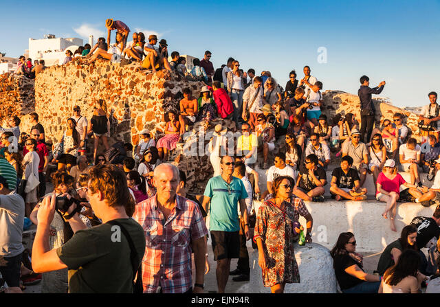 A crowd of people gathered together waiting to see the Sunset, Oia, Santorini (Thera), Greece - Stock Image