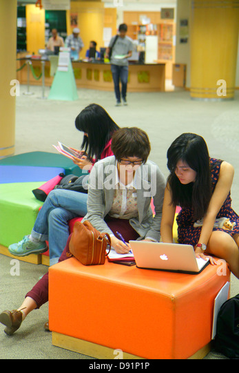 Singapore National University of Singapore NUS school student campus Central Library Asian woman Apple notebook - Stock Image