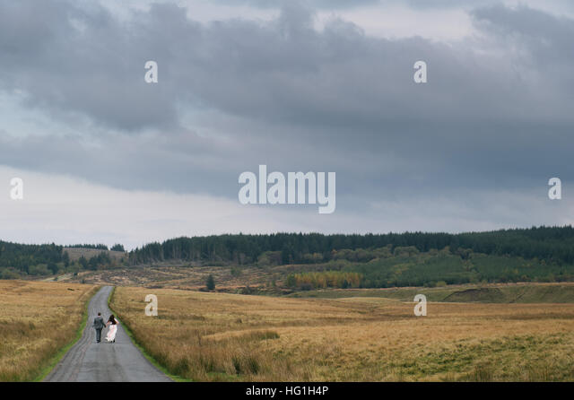 A couple of newlyweds run down a road in dramatic landscape of the Brecon Beacons National Park, Wales, UK. - Stock Image