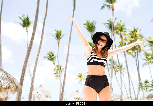 Woman on beach against palm trees - Stock Image