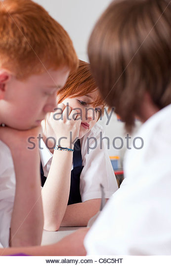 Bored students sitting together in classroom - Stock Image
