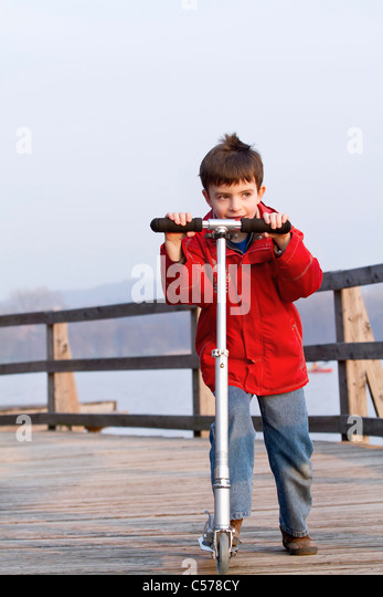 Boy riding scooter on dock over lake - Stock Image