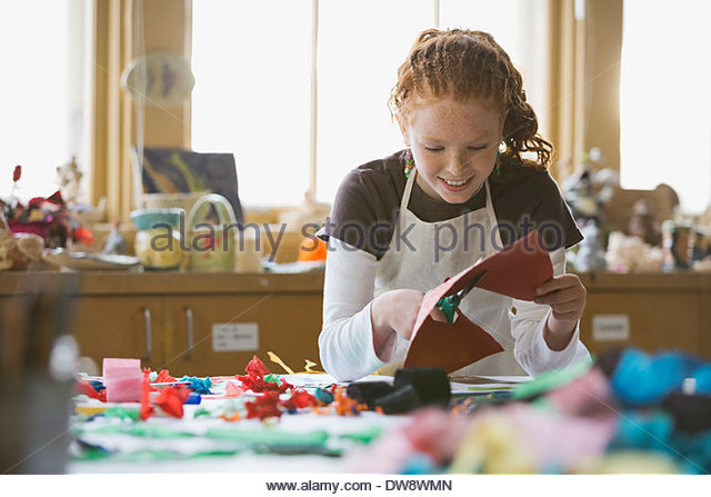 Girl cutting paper in art class - Stock Image