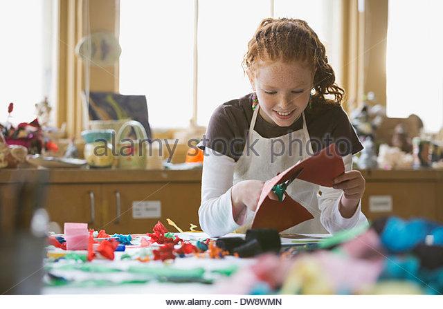 Girl cutting paper in art class - Stock Image