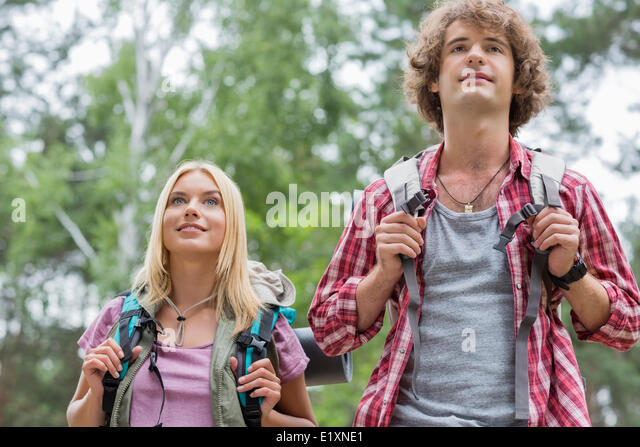 Young couple looking away while hiking in forest - Stock Image