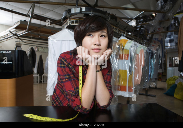 Woman working in the laundrette - Stock-Bilder