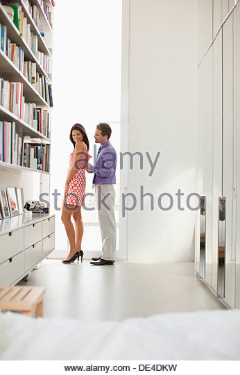 Man zipping wifeÂ's dress for her - Stock Image