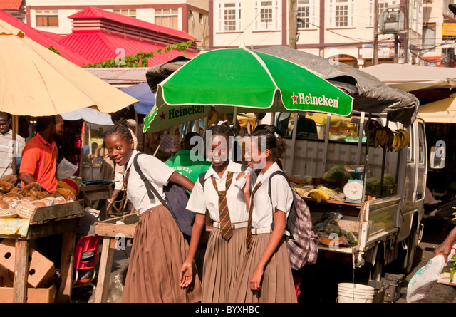 School girls in uniform at produce stand in downtown St Georges, Grenada, eastern caribbean - Stock Image