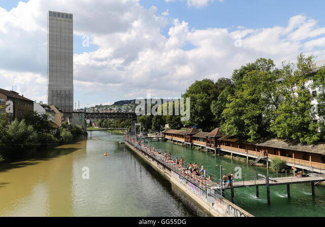 People enjoy the summer sunshine next to the Limmat River in at Letten in Zürich, Switzerland. - Stock Image