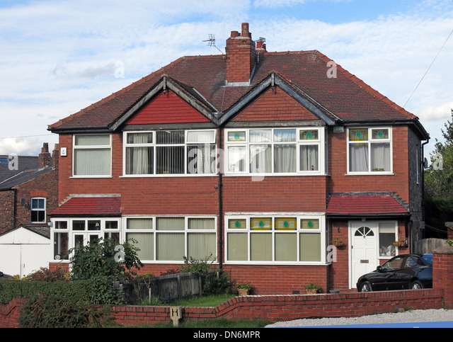 Typical 1930s English brick built semi-detached house with triangles over bedrooms, front garden shared chimney - Stock Image