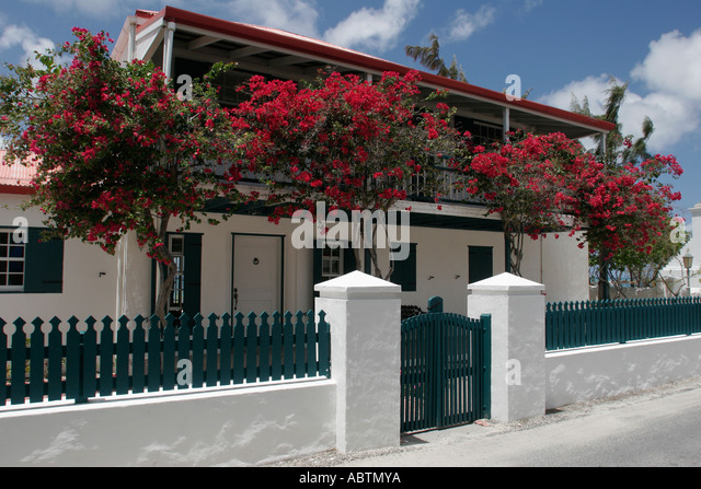 Grand Turk Cockburn Town Duke Street house wall fence flowering trees - Stock Image