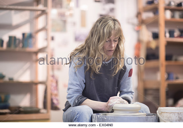 Female potter forming clay on pottery wheel in workshop - Stock Image