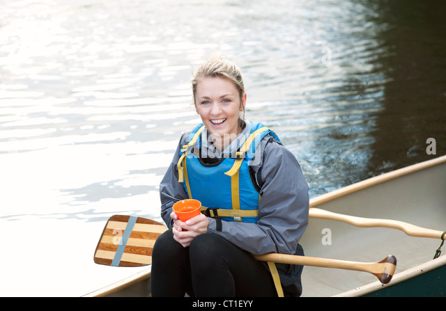 Woman having coffee in canoe - Stock Image