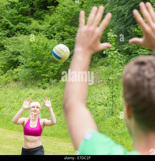 Young couple playing volleyball in park. - Stock Image
