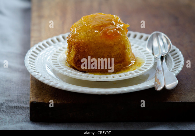 ndividual St Clements pudding on cream ribbon plates with vintage cutlery. - Stock Image