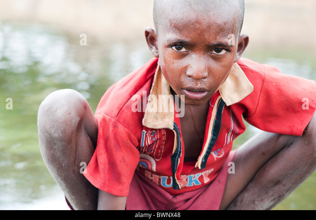Indian street boy washing himself and drinking water in a river in the Indian countryside - Stock Image