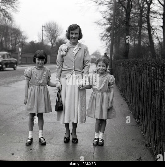 1950s historical picture of a mother standing on a pavement with her two young children, little girls in dresses, - Stock Image