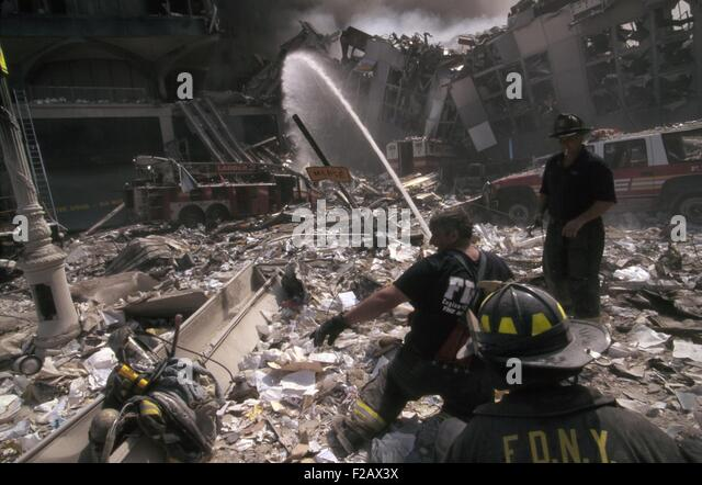 Fire fighters set up a hose amid smoking rubble following September 11th terrorist attack on World Trade Center. - Stock-Bilder