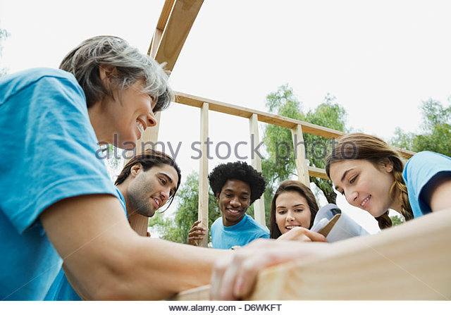 Low angle view of volunteers reviewing checklist while making wooden frame at park - Stock Image