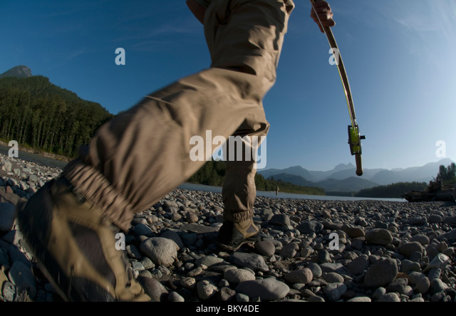 A man holding a fishing rod walks to the river to go fly fishing in Squamish, Brithish Columbia. (motion blur) - Stock Image