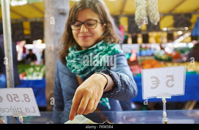 Young woman buying goods at market stall - Stock-Bilder