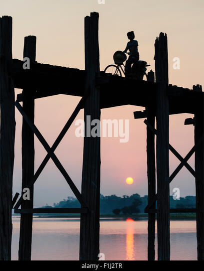 Silhouette of a Burmese woman on a bicycle riding over U Bein Bridge at sunset. - Stock-Bilder