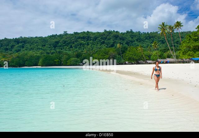 Tourist wandering along the turquoise water and white sand at the Champagne beach, Island Espiritu Santo, Vanuatu, - Stock-Bilder