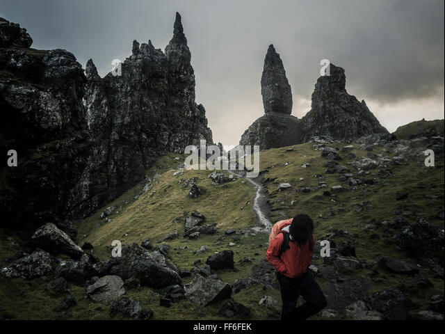 Two people with rucksacks on a narrow path rising to a dramatic landscape of rock pinnacles - Stock Image