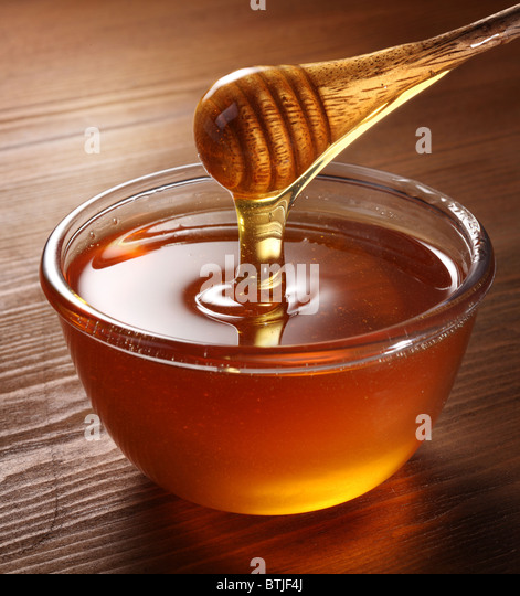 Honey pouring from drizzler into the bowl. Bowl is on a wooden table. - Stock Image