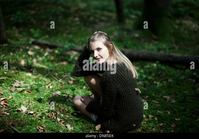 Girl squatting on the forest floor, portrait - Stock Image