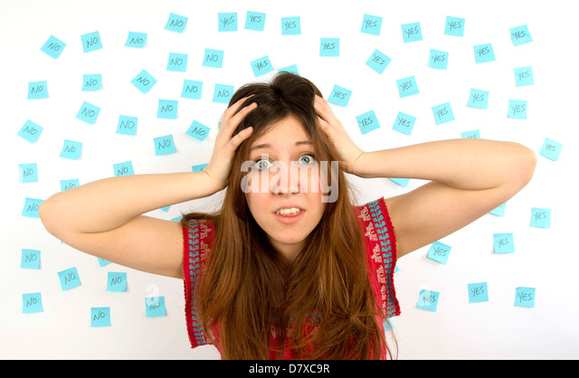 Young woman with nose ring with blue sticky notes with yes no thinking about decision making - Stock Image