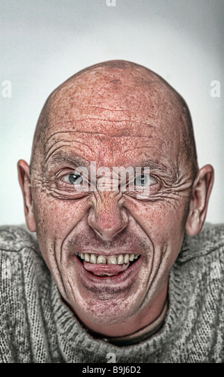 stylised portrait photograph of crazy bald man with his tongue sticking out - Stock Image