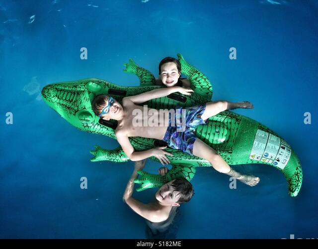 Children pose for a family photograph as they play in a swimming pool with an inflatable bed in the shape of a crocodile. - Stock-Bilder