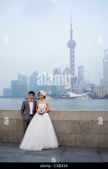 Young married couple posing for wedding photographs on The Bund with skyline of Pudong financial district  rear - Stock Image