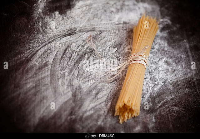 Spaghetti on wooden table with flour - Stock Image