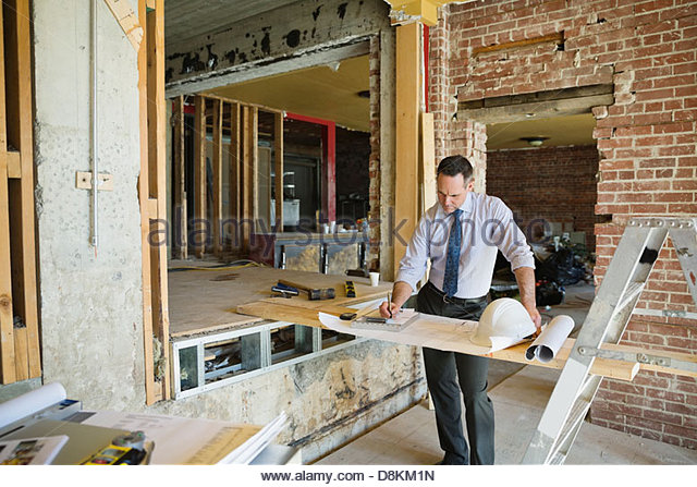 Male architect writing notes on work order at construction site - Stock Image