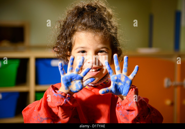 Kids, school and education, happy female child having fun and painting in kindergarten, showing hands to camera - Stock Image