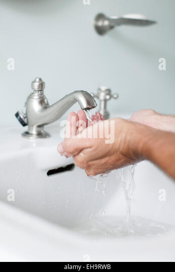 Man cupping hands beneath water running from bathroom faucet - Stock Image