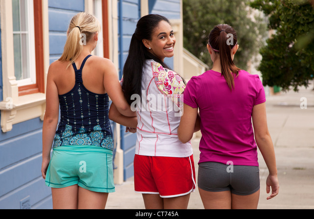 Three girls in fitness clothing are walking down the street. - Stock-Bilder