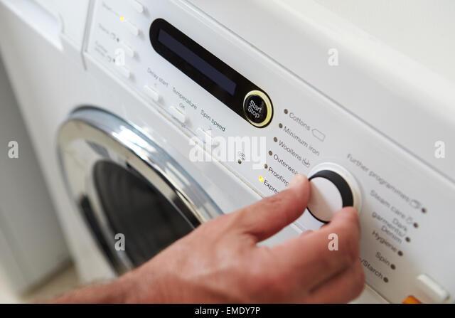 Close Up Of Man Choosing Cycle Program On Washing Machine - Stock Image