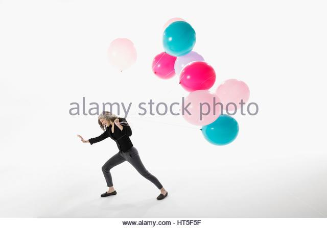 Woman pulling vibrant balloons against white background - Stock-Bilder