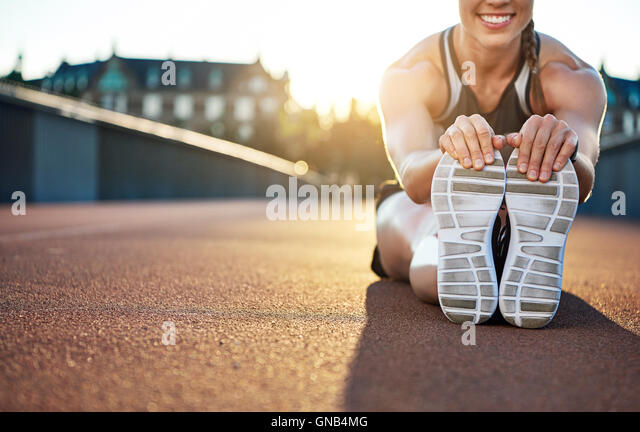 Woman athlete grabs her shoes as she stretches and smiles while seated on jogging path - Stock Image