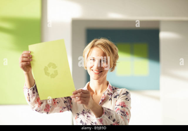 Woman looking at green sheet with logo - Stock Image