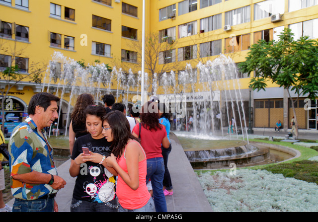 Lima Peru Plaza de Armas public square park fountain Hispanic man girl teen father daughter student cell phone texting - Stock Image