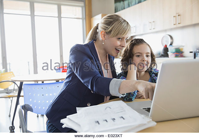 School girl and teacher using laptop in classroom - Stock Image