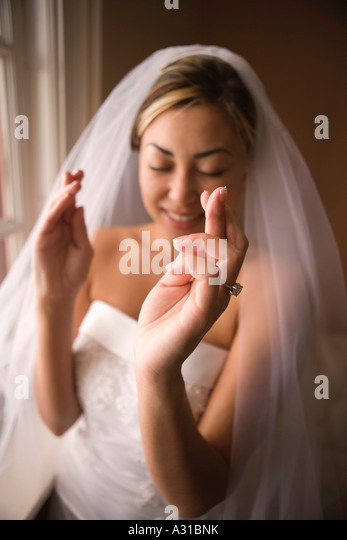 Bride standing with eyes closed and fingers crossed - Stock-Bilder